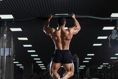 Modèle masculin de forme physique musculaire d'athlète tirant vers le haut sur la barre horizontale photographie stock libre de droits