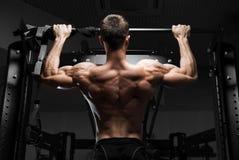 Modèle masculin de forme physique musculaire d'athlète tirant vers le haut sur la barre horizontale Image libre de droits
