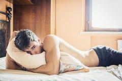 Modèle masculin sexy sans chemise seul se trouvant sur son lit photographie stock