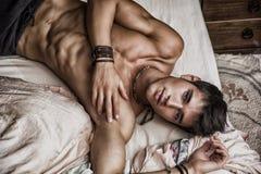 Modèle masculin sexy sans chemise seul se trouvant sur son lit image stock
