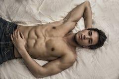 Modèle masculin sexy sans chemise seul se trouvant sur son lit photos stock
