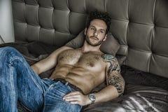 Modèle masculin sexy sans chemise seul se trouvant sur son lit photo stock