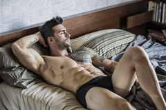 Modèle masculin sexy sans chemise seul se trouvant sur son lit photos libres de droits
