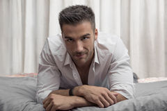 Modèle masculin sexy seul se trouvant sur son lit Photographie stock