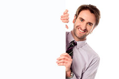 Modèle masculin tenant le panneau blanc vide d'annonce Image stock