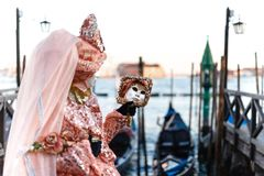 Modèle masqué vénitien du carnaval 2019 de Venise avec des gondoles à l'arrière-plan photos stock