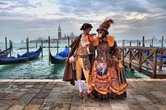 Modèle masqué vénitien du carnaval 2015 de Venise avec des gondoles à l'arrière-plan près de la plaza San Marco, Venezia, Italie photo libre de droits