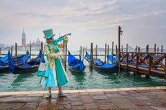 Modèle masqué vénitien du carnaval 2015 de Venise avec des gondoles à l'arrière-plan près de la plaza San Marco, Venezia, Italie photographie stock libre de droits
