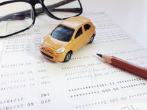 Modèle miniature de voiture, crayon, lunettes et carnet de compte d'épargne d'épargnes ou relevé de compte financier sur le fond  images stock
