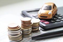 Modèle miniature de voiture, pile de pièces de monnaie, calculatrice et livre de comptes d'économie ou relevé de compte financier photographie stock libre de droits