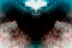 Modèle mystique de fumée multicolore de rouge et de bleu sous forme de corbeau avec les ailes ouvertes de couleur noire créant un photos libres de droits