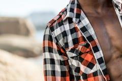 Modèle noir africain avec six paquets dans la chemise à carreaux déboutonnée Photographie stock libre de droits