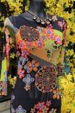 Modèle occupé sur la robe avec les fleurs colorées derrière Image stock
