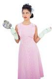 Modèle perplexe de cheveux noirs tenant une casserole et portant les gants en caoutchouc Photographie stock