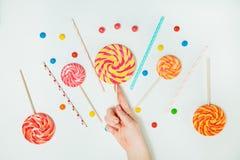 Modèle plat étendu par fond blanc de main de lucette de bonbons au chocolat Photographie stock