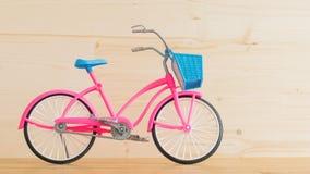 Modèle rose de bicyclette du ` s d'enfants sur le plancher en bois Photo libre de droits