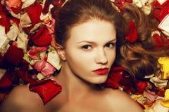 Modèle roux à la mode (de gingembre) dans des pétales de rose Images stock