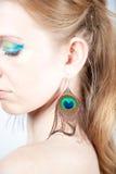 Modèle roux avec des boucles d'oreille de paon Photographie stock