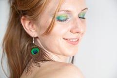 Modèle roux avec des boucles d'oreille de paon Photos stock