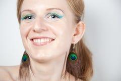 Modèle roux avec des boucles d'oreille de paon Image libre de droits
