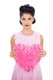 Modèle sérieux de cheveux noirs tenant un oreiller en forme de coeur rose Photos libres de droits