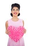 Modèle satisfait de cheveux noirs tenant un oreiller en forme de coeur rose Image stock