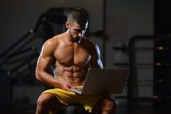 Modèle sportif musculaire Use Computer de forme physique de Bodybuilder Image stock