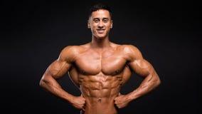 Modèle sportif souriant fort de forme physique d'homme montrant des muscles sur le fond foncé photos stock