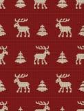 Modèle tricoté sans couture avec des cerfs communs et des sapins sur un fond rouge illustration libre de droits