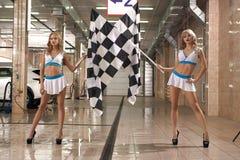 Modèles aux longues jambes chauds avec des drapeaux de course à la station de lavage Images libres de droits