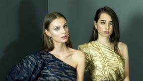 Modèles avec le maquillage chic dans des robes sur une épaule posant professionnellement pour la séance photos banque de vidéos