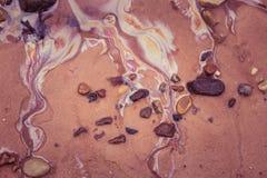 Modèles colorés d'huile dans le sable de plage Modèles de pollution sur le rivage de la mer baltique Photographie stock