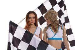 Modèles dans l'uniforme avec les drapeaux à carreaux de course Photos stock