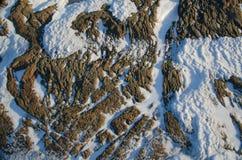 Modèles dans la neige et la roche Images libres de droits