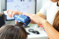 Modèles de coiffure de coiffeur utilisant le redresseur Photos libres de droits