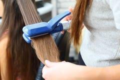 Modèles de coiffure de coiffeur utilisant le redresseur Image stock