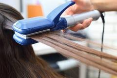 Modèles de coiffure de coiffeur utilisant le redresseur Images libres de droits
