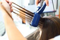 Modèles de coiffure de coiffeur utilisant le redresseur Images stock