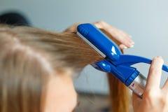 Modèles de coiffure de coiffeur utilisant le redresseur closeup Foyer sélectif Photos libres de droits