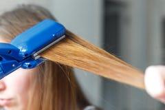 Modèles de coiffure de coiffeur utilisant le redresseur closeup Foyer sélectif Image libre de droits