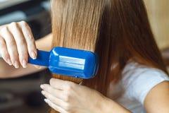 Modèles de coiffure de coiffeur utilisant le redresseur closeup Foyer sélectif Image stock