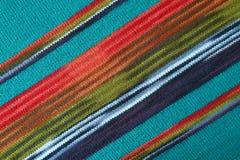 Modèles diagonaux et la texture du bleu de turquoise avec et vert tissu de laine tricoté paralpaga rayé rouge images libres de droits