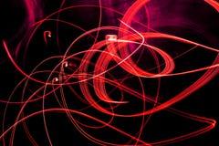 Modèles en spirale lumineux des bandes légères sur un fond noir photo stock