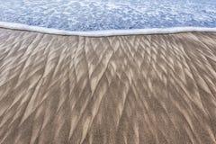 Modèles et vague de sable sur la plage Photo libre de droits