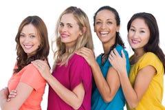 Modèles gais dans une ligne posant avec les T-shirts colorés Photos libres de droits