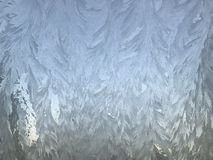 Modèles gelés de glace sur une fenêtre photographie stock libre de droits