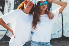 Modèles utilisant le T-shirt simple et les lunettes de soleil posant au-dessus du wa de rue Photo stock
