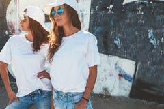 Modèles utilisant le T-shirt simple et les lunettes de soleil posant au-dessus du wa de rue Image libre de droits