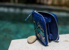 Mod kobiet akcesoria Luksusowy handmade snakeskin pytonu portfel Odgórny widok, błękitny basen, lekkiej wody tło Bezpłatny opróżn obraz stock