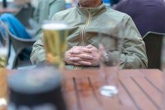 Mod. met wapens wordt gezeten clapsed en pint van lagerbier dat Royalty-vrije Stock Foto's